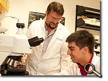 Professor and student scholar conducting cellular research in lab photo
